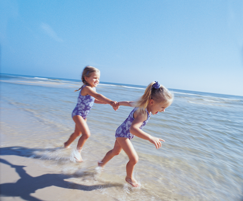 Little girls polaying together in the water at the beach