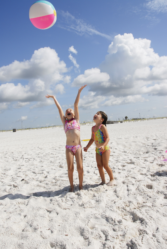 Little girls playing with beach ball on sand