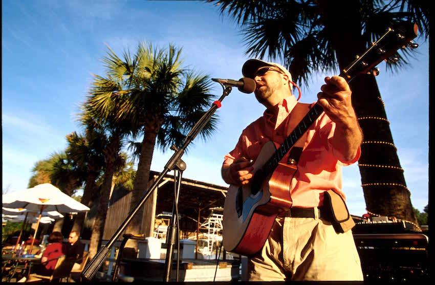 Man singing and playing guitar at Calypsos